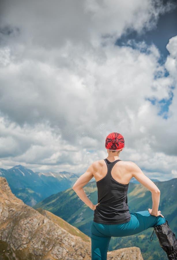 Caminante de la mujer que se coloca en el top de la montaña Actitud trasera imagen de archivo