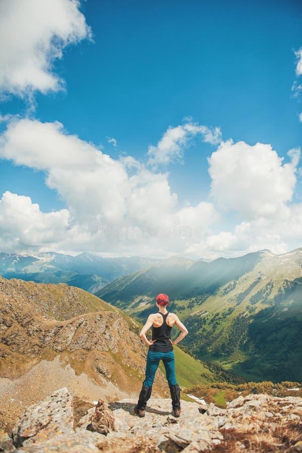 Caminante de la mujer que se coloca en el top de la montaña Actitud trasera imágenes de archivo libres de regalías