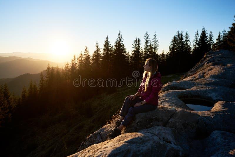 Caminante de la mujer que se sienta en el canto rodado en las monta?as en la puesta del sol fotografía de archivo