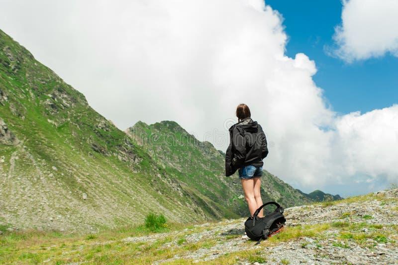 Caminante de la señora joven con la mochila que se sienta en la montaña fotos de archivo