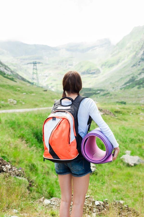 Caminante de la señora joven con la mochila que se sienta en la montaña foto de archivo