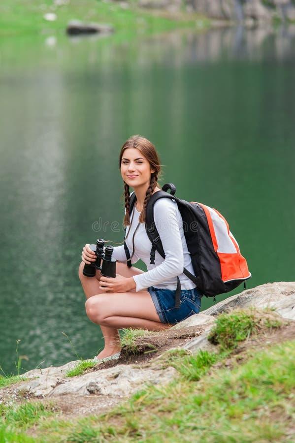 Caminante de la señora joven con la mochila que se sienta en la montaña imágenes de archivo libres de regalías
