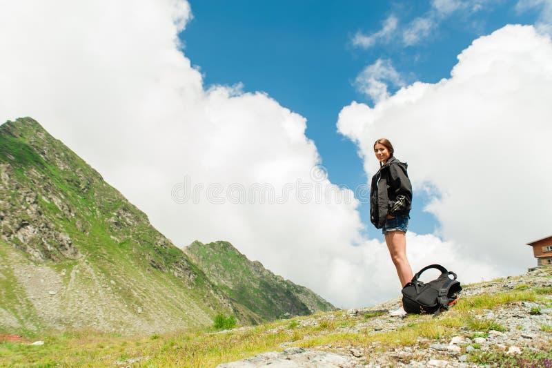 Caminante de la señora joven con la mochila que se sienta en la montaña fotografía de archivo libre de regalías