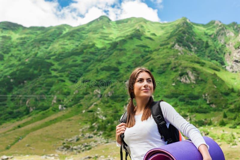 Caminante de la señora joven con la mochila que se sienta en la montaña imagenes de archivo