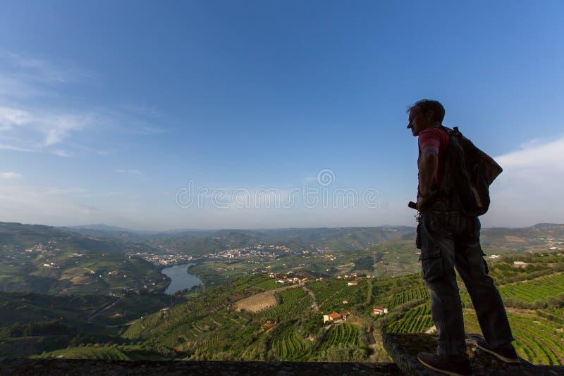 Caminante del hombre joven con la mochila que se relaja encima de una montaña y que disfruta de la vista del valle del Duero fotos de archivo