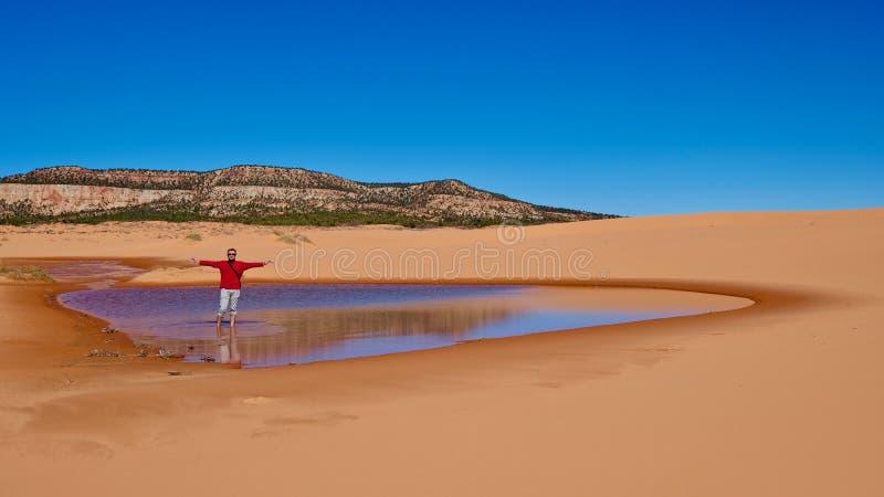 Caminante del hombre que vadea en poco lago fotografía de archivo libre de regalías