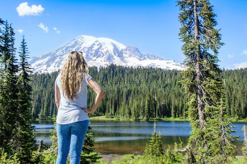 Caminante en las montañas que miran una vista escénica del Monte Rainier imagen de archivo