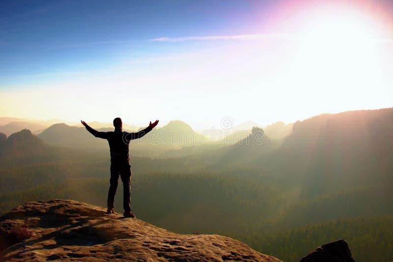 Caminante en negro Gesto del triunfo Turista alto en el pico de la roca de la piedra arenisca en el parque nacional Sajonia Suiza foto de archivo