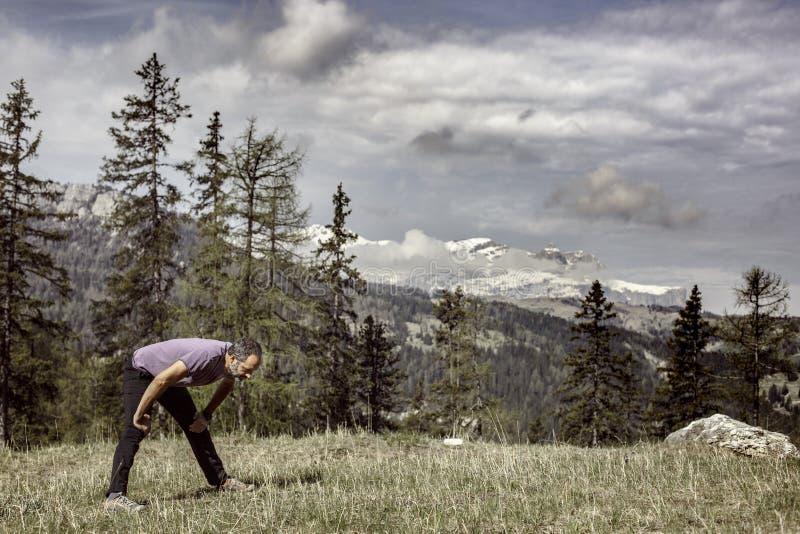 Caminante en un pasto del top de la montaña que ejercita y que estira imagen de archivo