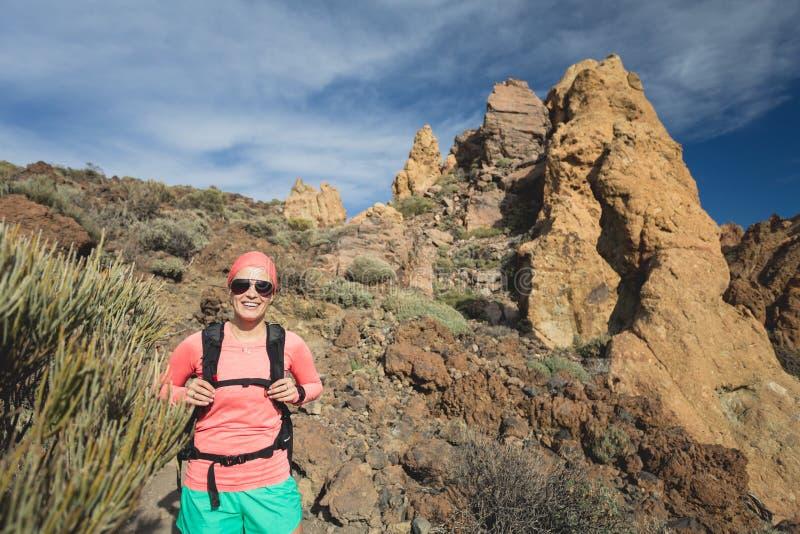 Caminante feliz de la muchacha que camina en la trayectoria de la montaña, aventura del backpacker foto de archivo