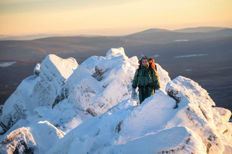 Caminante feliz de la mujer con la mochila que se coloca en el abd del pico de montaña que sonríe en el día de invierno frío Héro imagen de archivo libre de regalías