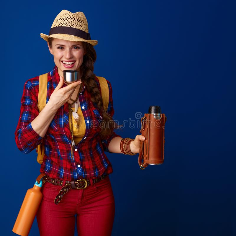 Caminante feliz de la mujer que bebe la bebida caliente de la botella de termo imagenes de archivo