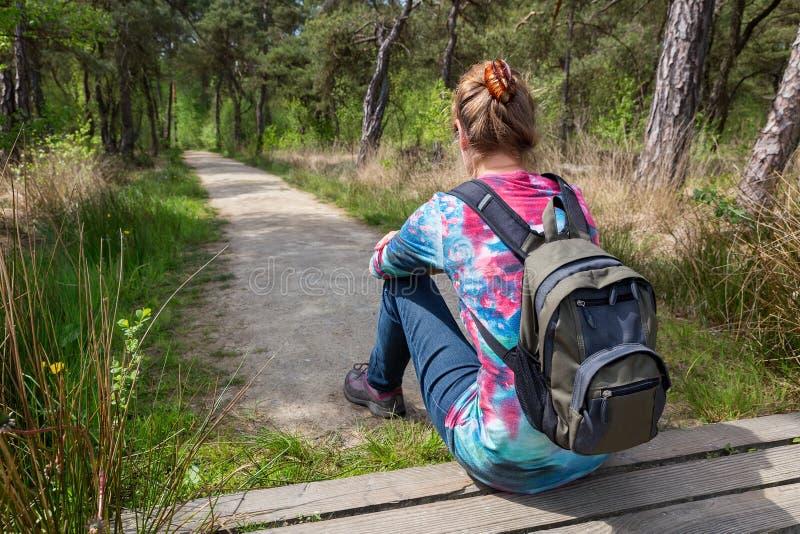 Caminante femenino con la mochila que se sienta en la trayectoria de bosque imagenes de archivo