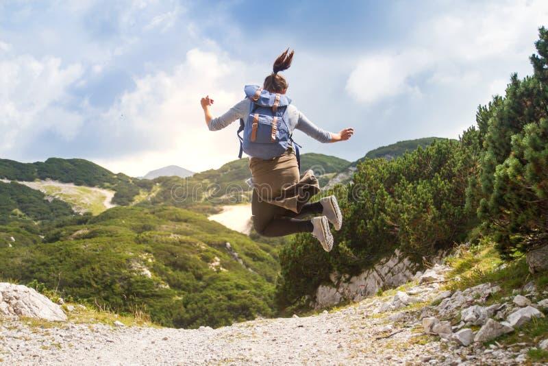Caminante femenino feliz que salta en montañas en un día soleado hermoso imagen de archivo