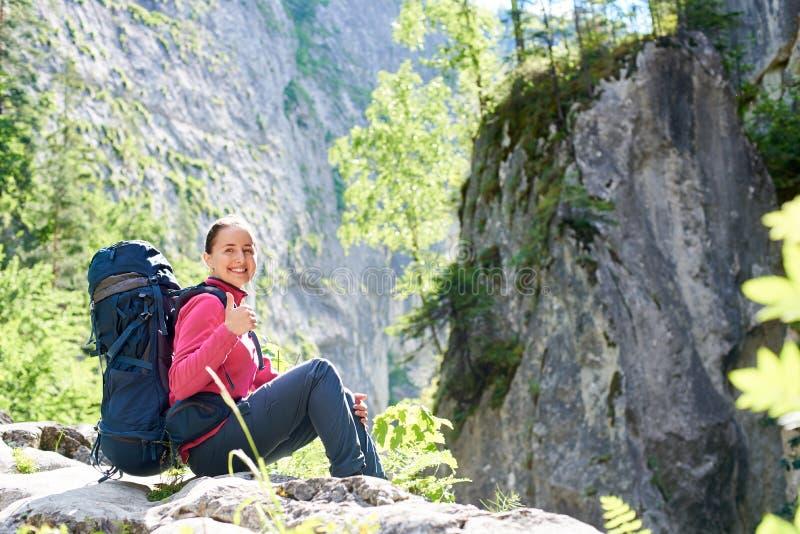 Caminante femenino que descansa en las montañas imágenes de archivo libres de regalías