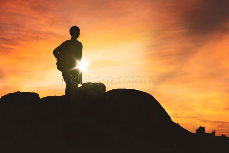 Caminante femenino que disfruta de la opinión de la puesta del sol sobre una colina imagen de archivo libre de regalías
