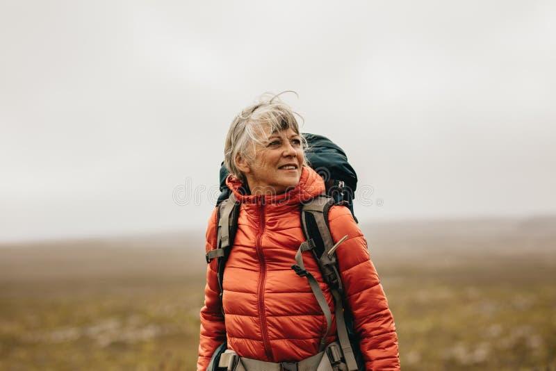 Caminante femenino que disfruta de la situación de la visión en una colina fotografía de archivo