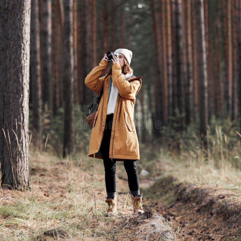 Caminante femenino que toma la foto mientras que camina en bosque foto de archivo libre de regalías