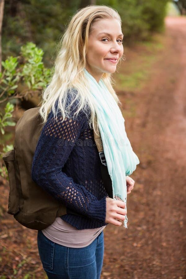 Caminante femenino sonriente que espera por el lado del camino fotos de archivo libres de regalías