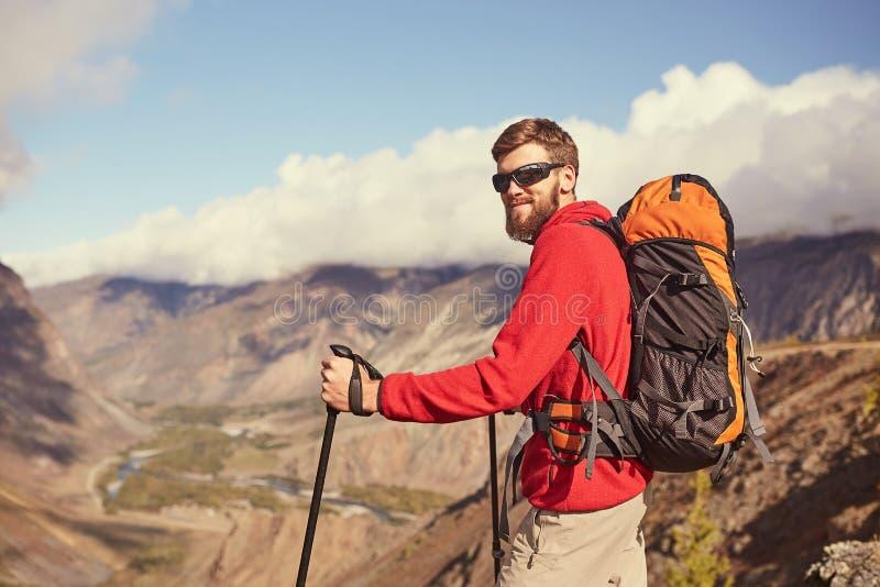 Caminante masculino barbudo joven hermoso que se coloca al borde de un barranco que mira lejos foto de archivo