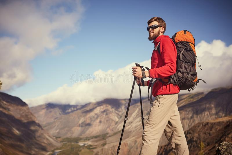 Caminante masculino barbudo joven hermoso que se coloca al borde de un barranco que mira lejos fotos de archivo