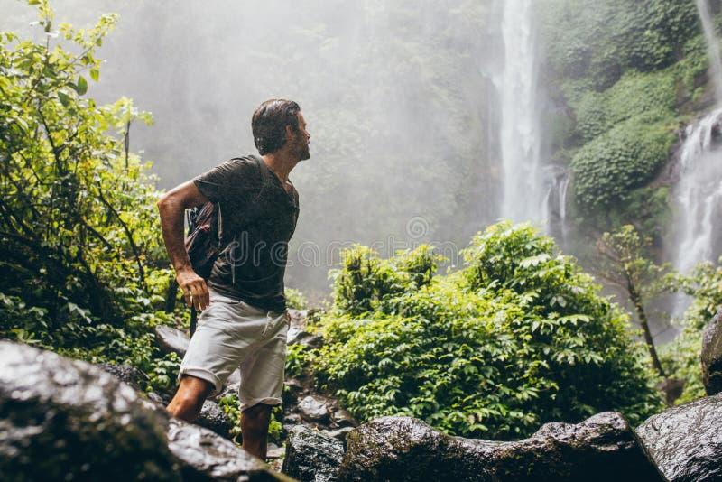 Caminante masculino cerca de la cascada durante la lluvia imagen de archivo