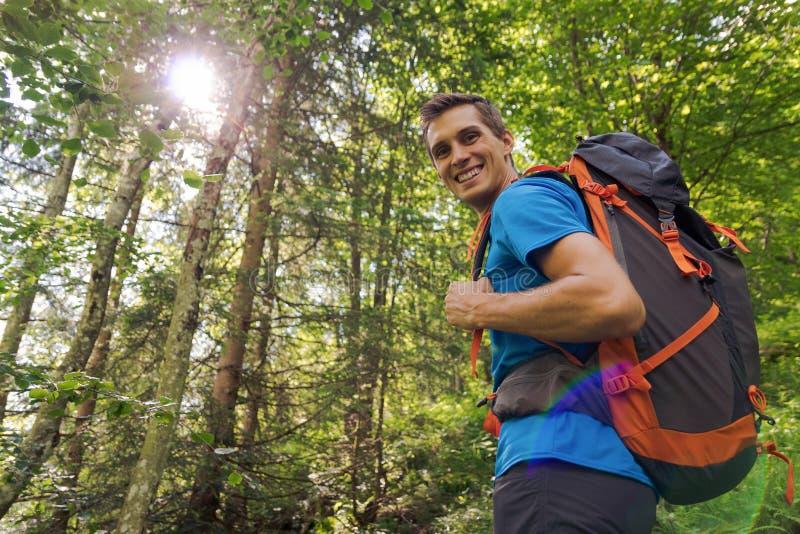 Caminante masculino con la mochila grande que sonríe a la cámara rodeada por los árboles y la luz del sol foto de archivo