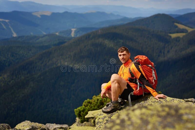 Caminante masculino joven con la mochila que se relaja encima de una montaña durante puesta del sol tranquila del verano imagen de archivo libre de regalías