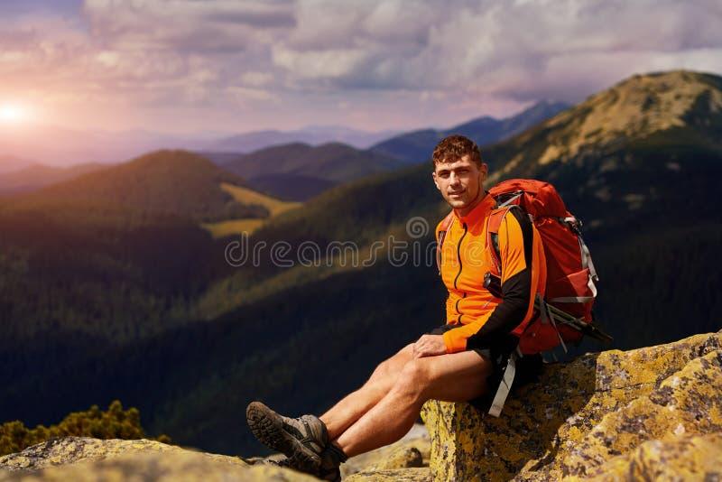 Caminante masculino joven con la mochila que se relaja encima de una montaña durante puesta del sol tranquila del verano fotos de archivo