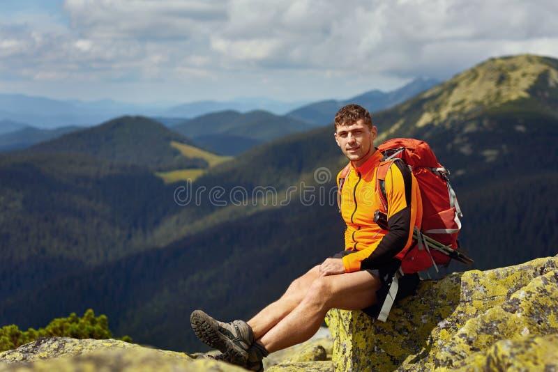 Caminante masculino joven con la mochila que se relaja encima de una montaña durante puesta del sol tranquila del verano imagenes de archivo
