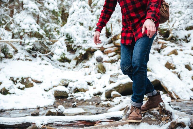 Caminante masculino que camina en el río de la montaña fotografía de archivo
