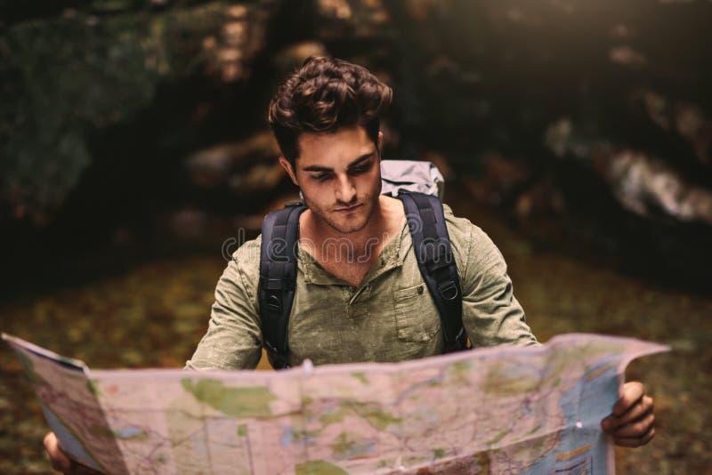 Caminante masculino que usa un mapa para localizar el destino fotos de archivo libres de regalías