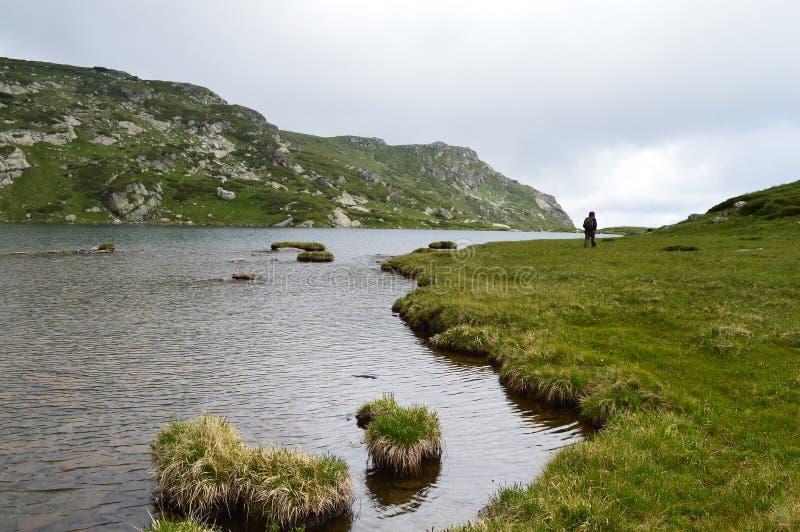 Caminante por un lago de la montaña en día nublado imágenes de archivo libres de regalías