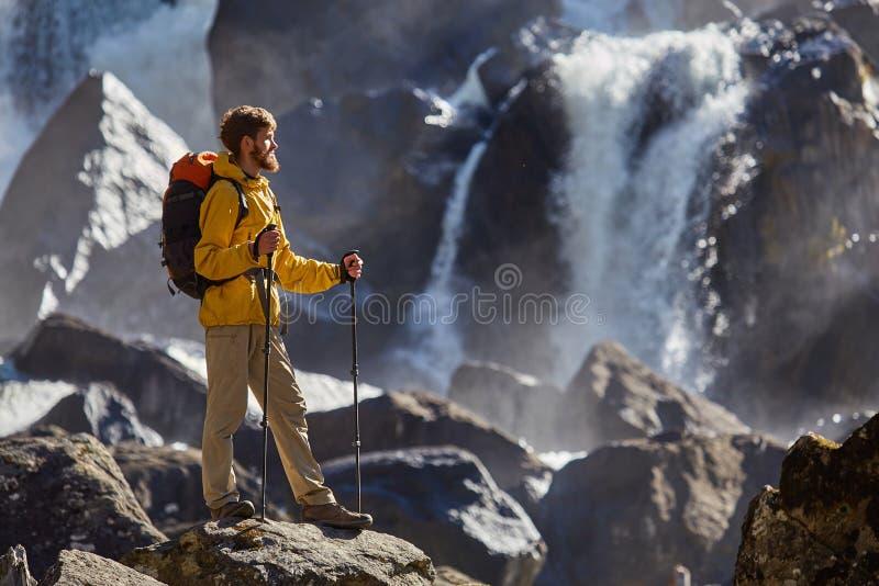 Caminante que camina con la mochila que mira la cascada foto de archivo libre de regalías