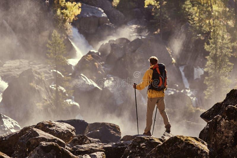 Caminante que camina con la mochila que mira la cascada imagen de archivo libre de regalías