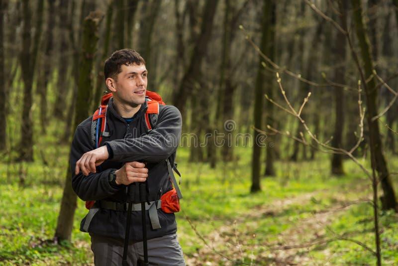 Caminante que lleva caminando la mochila y la chaqueta en alza en bosque imagen de archivo libre de regalías