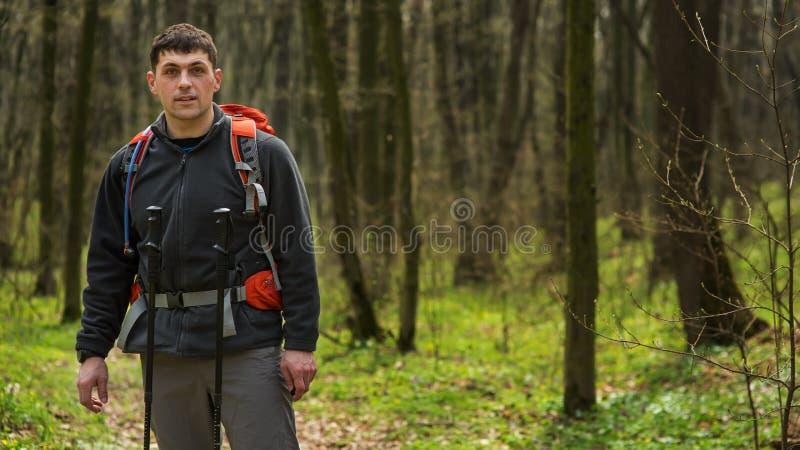 Caminante que lleva caminando la mochila y la chaqueta en alza en bosque imagen de archivo