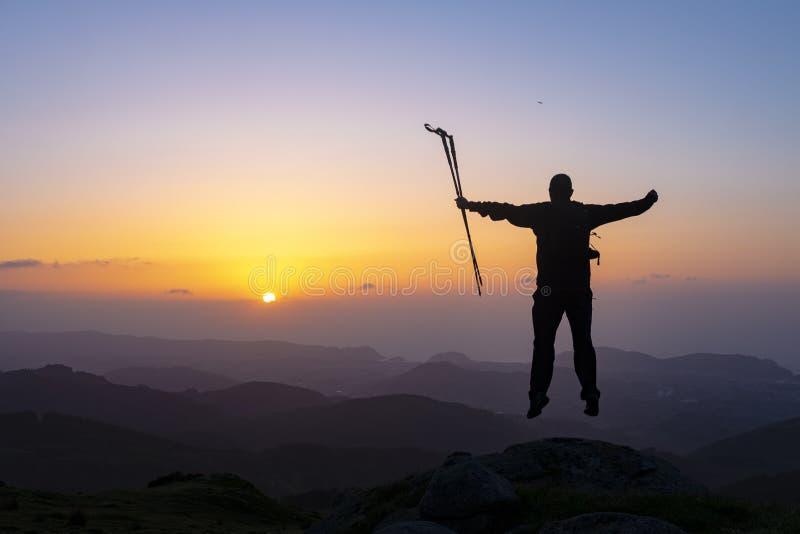 Caminante que se coloca encima de una montaña con las manos aumentadas y que disfruta de salida del sol foto de archivo