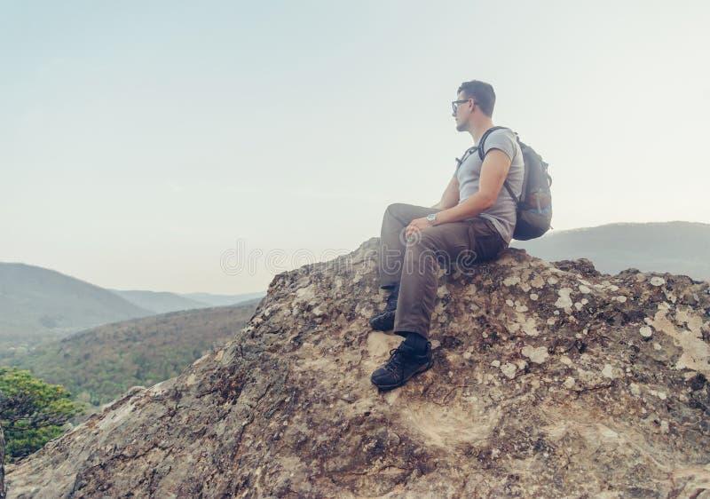 Caminante que se sienta en el pico de la roca fotografía de archivo libre de regalías