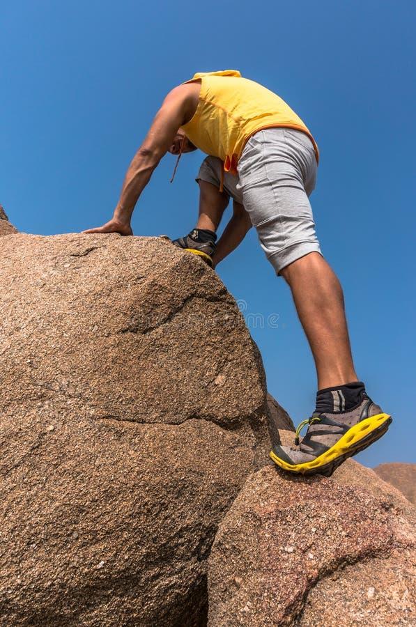 Caminante que sube en una roca fotos de archivo