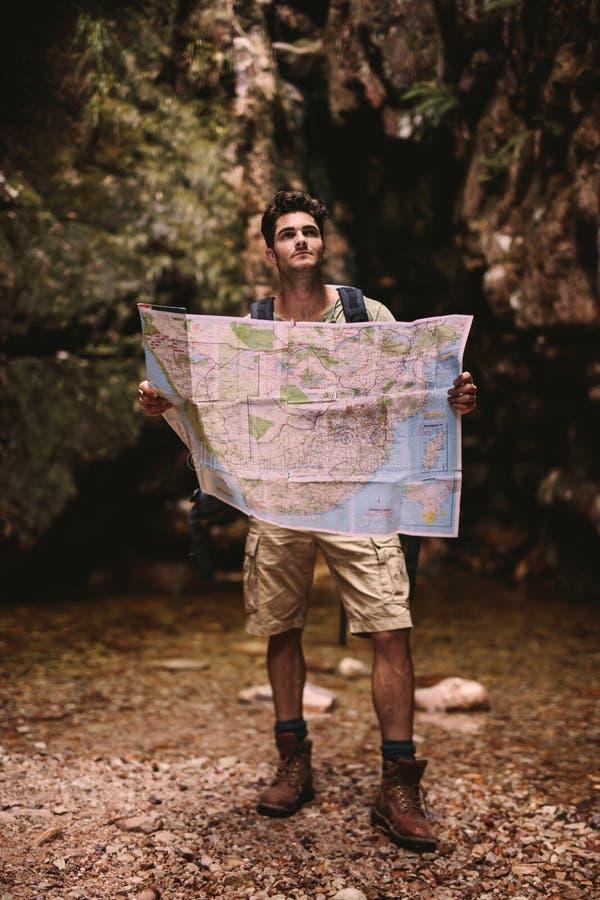 Caminante que usa un mapa para encontrar la ruta al destino imágenes de archivo libres de regalías