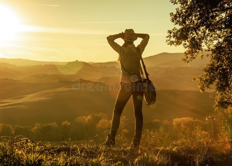 Caminante relajado de la mujer de la aventura que disfruta de puesta del sol en Toscana fotos de archivo