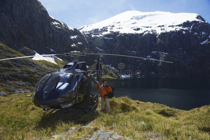 Caminantes con el helicóptero en el top de la montaña fotos de archivo