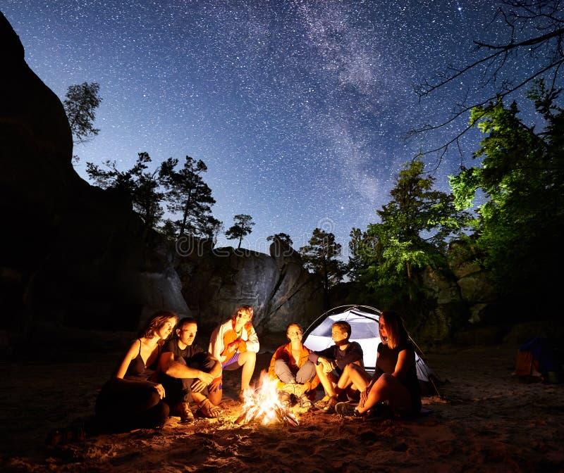 Caminantes de los amigos que descansan al lado del campo, hoguera, tienda en la noche imágenes de archivo libres de regalías