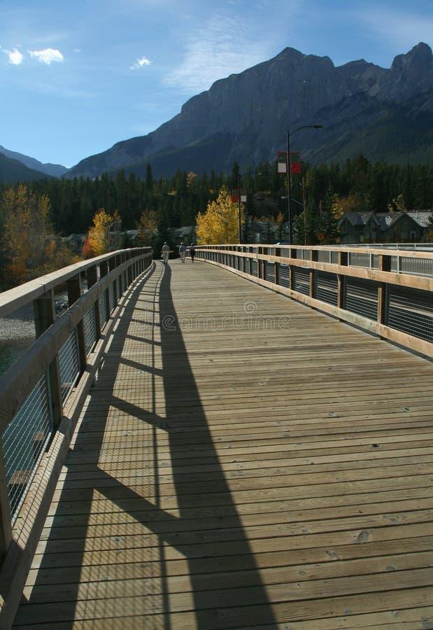 Caminantes en el puente sobre el río del arqueamiento fotos de archivo libres de regalías