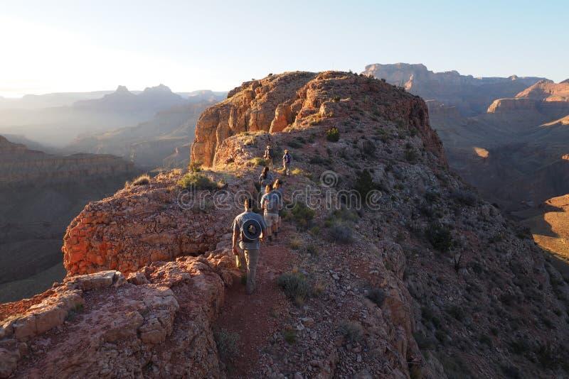 Caminantes en la puesta del sol en el Mesa de herradura en Grand Canyon imagen de archivo libre de regalías