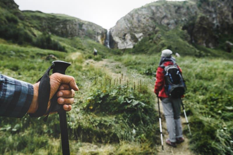 Caminantes en las montañas, emigrando a poste en la mano de un primer de la persona del viajero Concepto de las vacaciones de la  fotografía de archivo libre de regalías