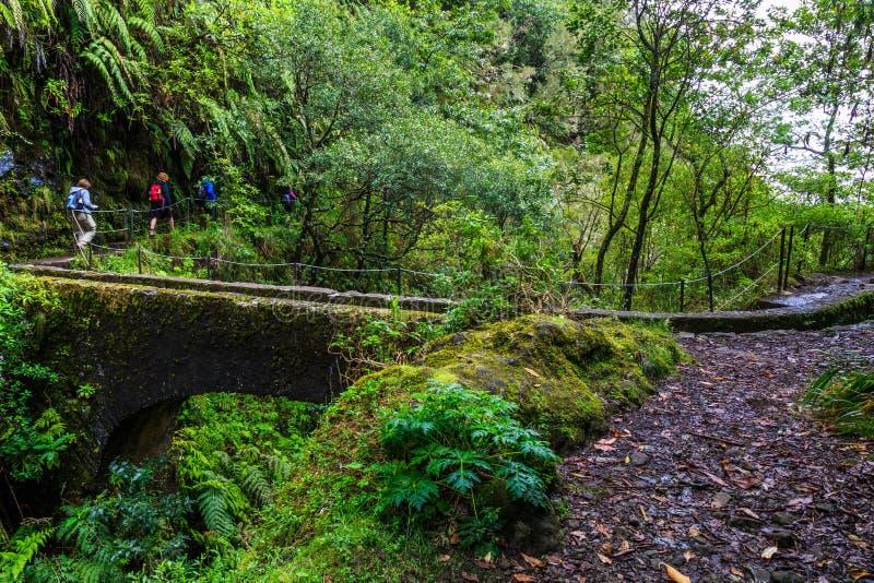 Caminantes que cruzan un puente viejo del arco a lo largo de un levada en la isla imagen de archivo libre de regalías