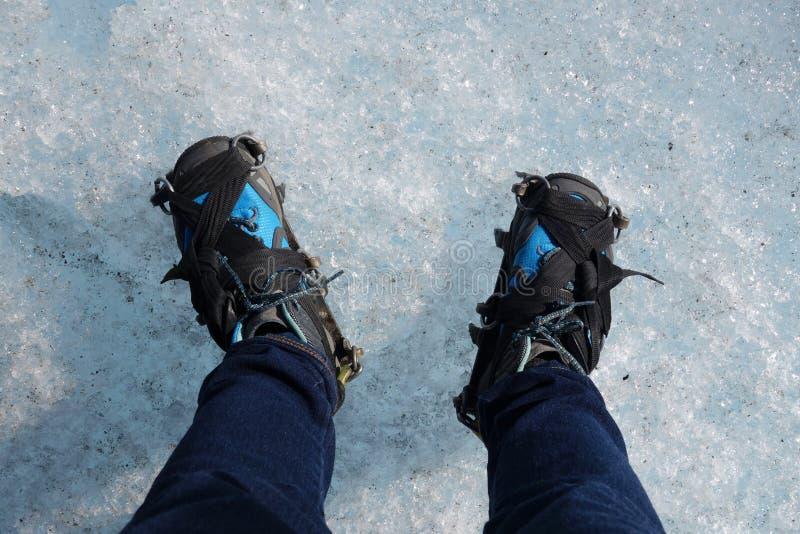 Caminar botas con el grampón en el hielo foto de archivo libre de regalías