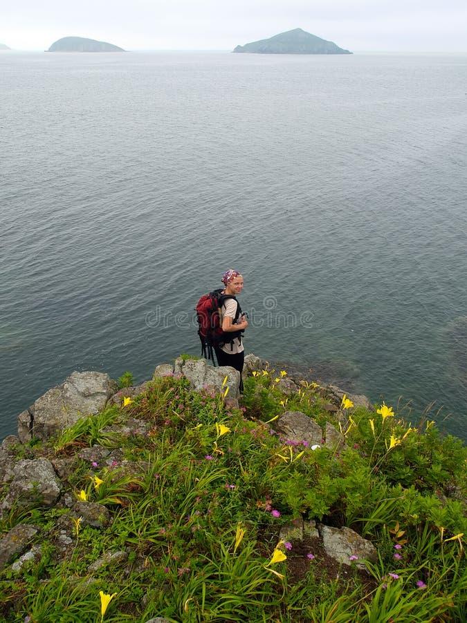 caminar a la muchacha en la roca del océano fotos de archivo